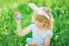 Cute funny girl with Easter eggs and bunny ears at garden. easter concept. Laughing child at Easter egg hunt. Child in park with basket full of eggs, spring stock photos