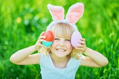 Cute funny girl with Easter eggs and bunny ears at garden. easter concept. Laughing child at Easter egg hunt. Child in park with basket full of eggs, spring stock photo