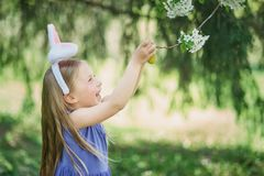 Cute funny girl with Easter eggs and bunny ears at garden. easter concept. Laughing child at Easter egg hunt. Baby caucasian celebrate celebration cheerful stock photos