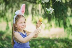 Cute funny girl with Easter eggs and bunny ears at garden. easter concept. Laughing child at Easter egg hunt. Baby caucasian celebrate celebration cheerful stock image