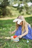 Cute funny girl with Easter eggs and bunny ears at garden. easter concept. Laughing child at Easter egg hunt royalty free stock photos