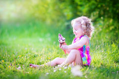 Cute funny girl eating ice cream in sunny garden Stock Photos
