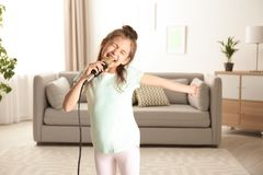 Cute funny girl with microphone in room stock photo