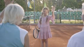 Cute funny girl with two pigtails playing tennis outdoors while her grandparents sitting near supporting her. Lovely. Child raising racket up. Summertime stock video footage