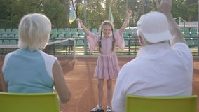 Cute funny girl with two pigtails won the tennis tournament. Her grandparents sitting near with their backs to camera. Cute funny girl with two pigtails won the stock footage