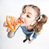 Cute funny girl with two pony tails eating pizza - wide angle shot Royalty Free Stock Photography