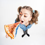 Cute funny girl with two pony tails eating pizza - wide angle shot Stock Images