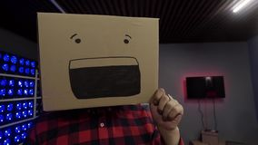 Cute funny guy puts carton box with drawn smile on his head at camera in studio. Cute funny guy with beard wearing stylish sunglasses and red checkered shirt stock footage