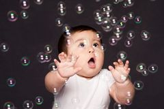 Cute funny happy amazed baby with bubbles royalty free stock images