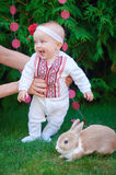 Cute funny happy baby with rabbit making his first steps on a green grass Royalty Free Stock Photos