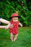 Cute funny happy baby in a red dress making his first steps on a green grass in a sunny Stock Images