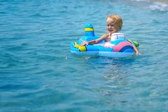 Cute funny happy little boy playing in the water waves at sea ocean on a sunny day stock image