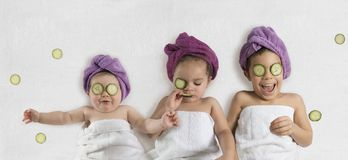 Funny kids and cucumber facials. Cute, funny kids in white towels and terry cloth bath turbans with cucumber face treatments stock photo
