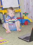 Cute funny little baby boy with long blonde curly hair playing on computer and mobile phone Stock Images
