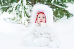 Cute funny little baby in winter park under big tree Royalty Free Stock Photo
