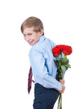 Cute funny little boy holding red roses behind his back smiling Royalty Free Stock Photography