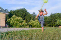 Cute funny little boy running to catch butterflies Royalty Free Stock Images