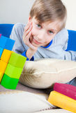 Cute funny little child resting on a sofa with colorful books and toys. Cute funny little child comfortably lying on a sofa with colorful books and toys smiling Stock Image