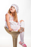 Cute, funny little girl on chair. Studio portrait on white Royalty Free Stock Photos