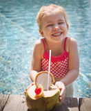 Cute funny little girl drinking coconut at the pool Royalty Free Stock Photos