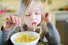 Cute funny little girl eating spaghetti Royalty Free Stock Photography