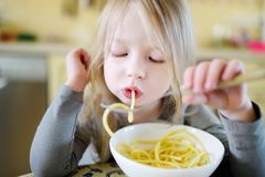 Cute funny little girl eating spaghetti stock photo
