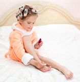 Cute funny little girl polishing her nails Royalty Free Stock Images