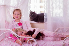 Cute funny little girls (sisters) play in bed, on the window sit Stock Photo