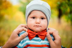 Cute funny little kid with a red bow tie at the neck. In autumn stock photography