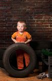 Cute and funny little mechanic with a tire Stock Image
