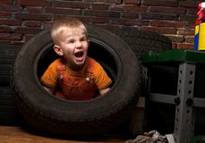 Cute and funny little mechanic with a tire Royalty Free Stock Image