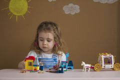 Cute funny preschooler little girl playing with construction toy blocks building a tower in kindergarten room. Royalty Free Stock Photo