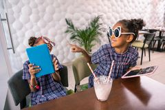 Cute funny siblings wearing bright sunglasses playing games on their tablets. Bright sunglasses. Cute funny siblings wearing bright sunglasses playing games on stock photo