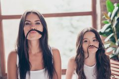 Cute funny sisters with beautiful long hdark hair are making fake mustache with their hair, they are having fun stock images