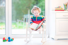 Cute funny toddler girl reading in rocking chair Stock Images