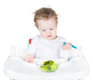 Cute funny toddler in a white high chair eating her vegetables f Royalty Free Stock Photography