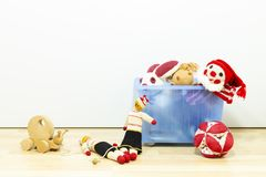 Assortment of cute vintage children toys. Cute and funny vintage children toys in a blue plastic box in front of a white wall. Assortment consists of a buffoon royalty free stock photography