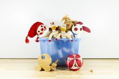 Assortment of cute vintage children toys. Cute and funny vintage children toys in a blue plastic box in front of a white wall. Assortment consists of a buffoon royalty free stock image