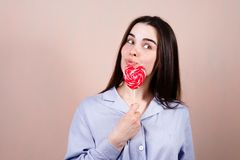 Cute funny woman with heart shaped lollipop stock photo