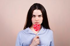 Cute funny woman with heart shaped lollipop royalty free stock photos