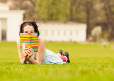 Cute and funny young female hiding behind book Stock Image