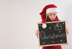 Cute funny young woman with blackboard in santa hat on white bac Royalty Free Stock Images