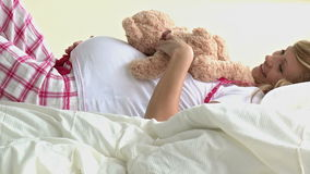 Cute future mom playing with a teddybear Royalty Free Stock Photo