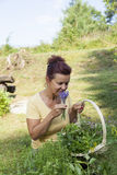 Cute gardener smelling organic herbs Stock Images