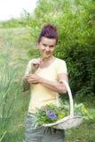 Cute gardener smelling organic herbs Stock Photos