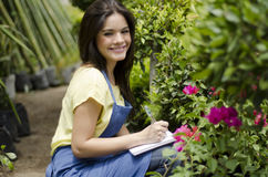 Cute gardener taking notes at work Royalty Free Stock Images