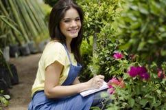 Cute gardener taking notes at work. Beautiful female gardener taking notes and doing inventory at work Royalty Free Stock Images