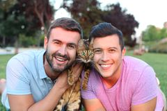 Cute gay couple with a bengal cat.  stock photo