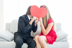 Cute geeky couple kissing and holding heart over faces Royalty Free Stock Photo