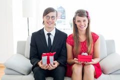 Cute geeky couple smiling and holding gift Royalty Free Stock Image